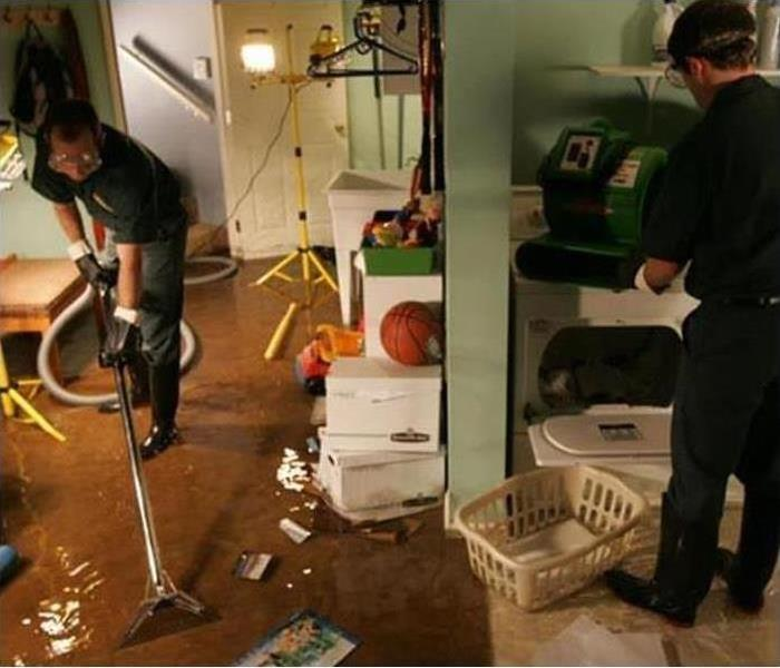 basement damaged by water, workers with vacuum extractor